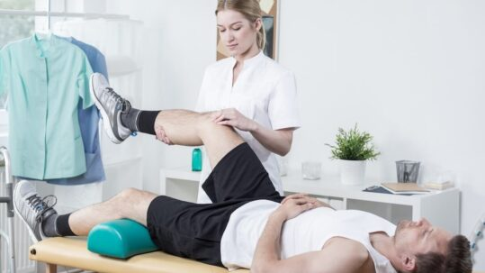 patient at physical therapy session doing leg exercises with physician